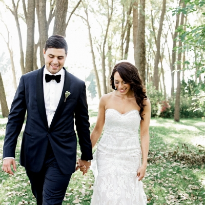 Bride and groom walking and holding hands at Cherry Beach in wooded area, in Toronto