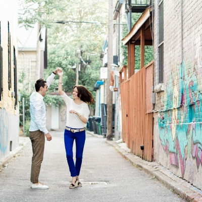 Couple dancing in the alley during engagement session in Kensington Market Toronto